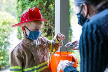 Young boy dressed up as firefighter recieves candy while trick-or-treating